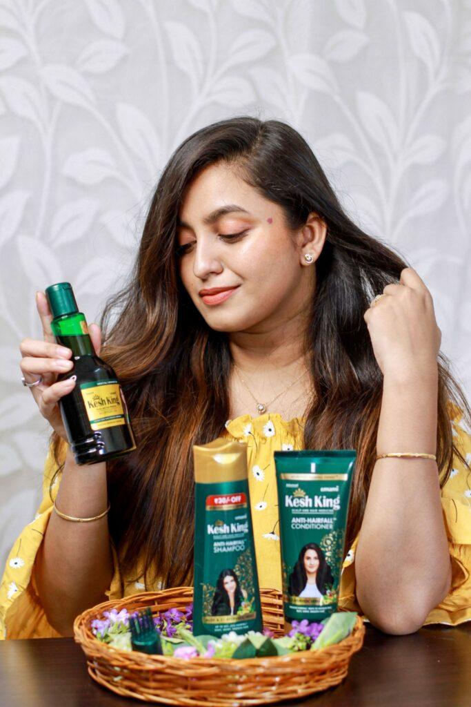 A Girl having good hair advertising Kesh King Ayurvedic Oil, Shampoo & Conditioner